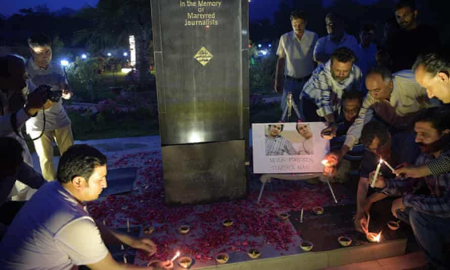 Journalists light candles next to a photograph of AFP photographer Shah Marai, who was killed along with other journalists in a targeted suicide bombing in Afghanistan on Monday