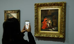 A woman takes a photo of a painting by Delacroix at the Louvre in Paris.