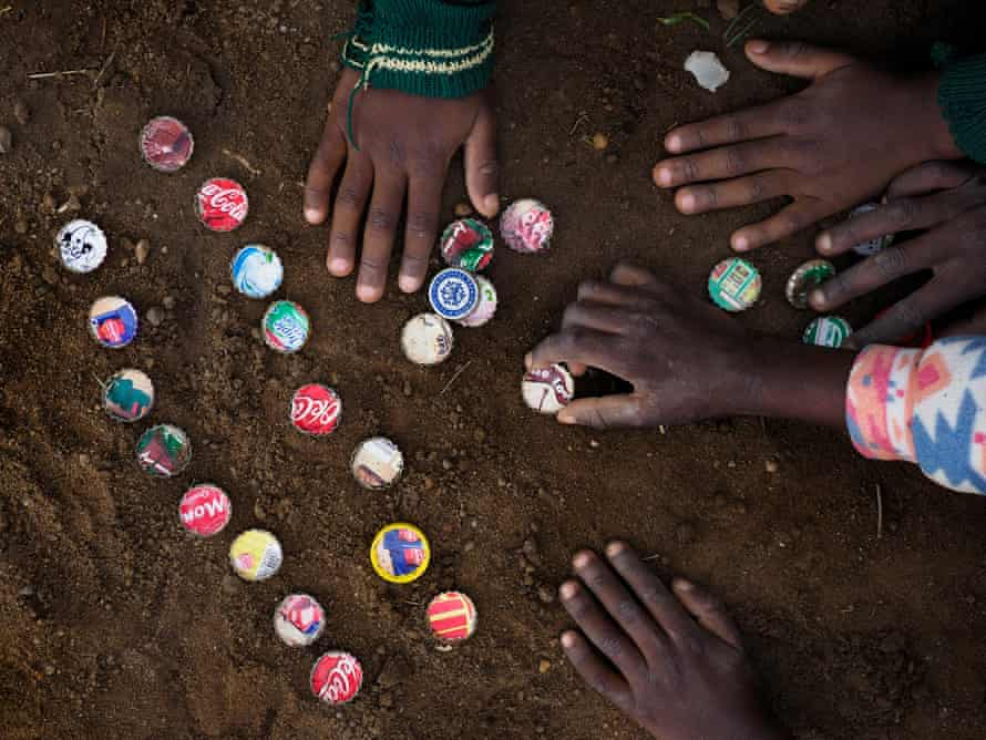 Children playing with bottle tops in the dust in Chowa township in Kabwe