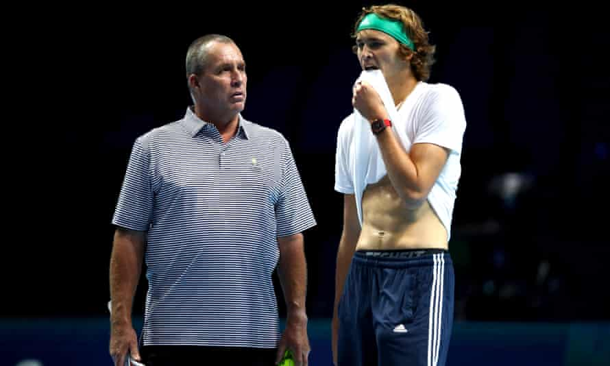 Alex Zverev in tennis clothes and bandana, pulling the bottom of his white T-shirt up into his mouth, standing with Ivan Lendl.