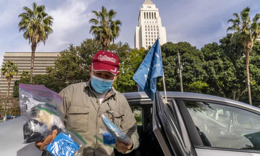 Jose Luis Guevara, a member of the Mobile Workers Alliance, shows personal protective equipment he provides freely to ride-sharing customers for their safety, outside Los Angeles City Hall.