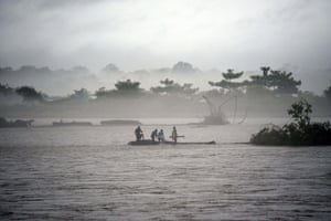 Indian men catch a tree in the flooded Manas river, following heavy rainfall in the district of Baksa.