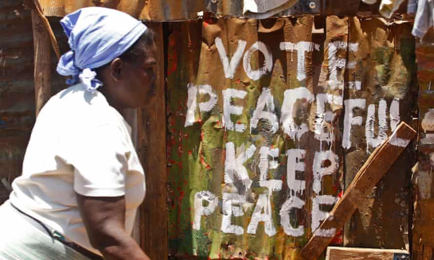 Woman walks past message of peace in Kibera, Nairobi