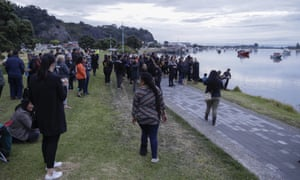 Locals sing during sun rise as they wait for the return of the victims after the White Island eruption to be returned to Whakatane.
