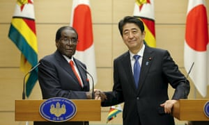 Japan's prime minister Shinzo Abe shakes hands with Zimbabwean president Robert Mugabe after a press briefing in Tokyo.