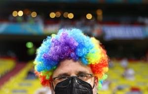 A fan wears a rainbow wig inside Allianz Arena