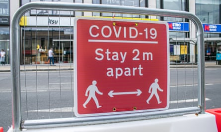 A 'Covid-19 stay 2 metres apart' sign is seen in Wimbledon town centre