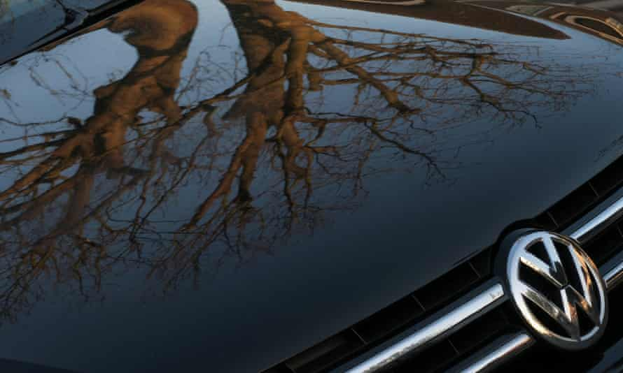 A Volkswagen vehicle with tree branches reflected on the bonnet
