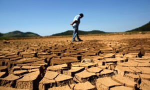 A worker from the São Paulo state company that provides water and sewage services inspects cracked ground near Jaguary dam, Braganca Paulista.