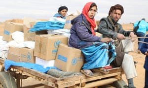 A Syrian man and a woman sit on a cart loaded with supplies delivered by the World Food Programme to the Rukban settlement.