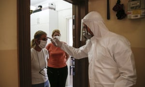 A contact tracer with Turkey's health ministry, clad in protective gear, visits a home in Istanbul. It is expected that New York's contact tracers will do most of their work on the phone.