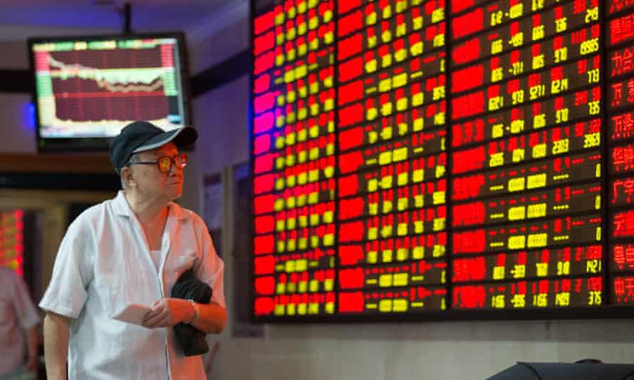 A man watches a screen with share prices in Nanjing, eastern China.