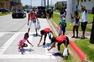 Children pick up candy thrown from a parade float during a Juneteenth parade in Galveston, Texas