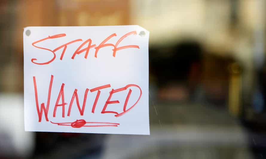 A 'staff wanted' sign in a restaurant window