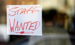 Handwritten 'Staff wanted' sign on shop window