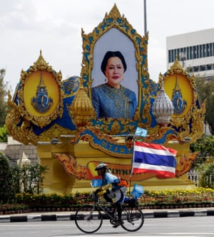 A cyclist passes a picture of Queen Sirikit at the Victory Monument as he takes part in the 'Bike for Mom' mass bicycle ride.