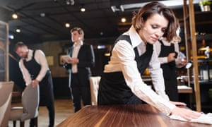 Serious busy young waitress and her colleagues preparing restaurant for opening