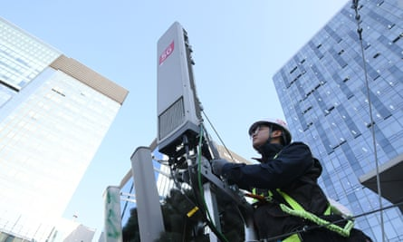 A technician of South Korean telecom operator KT checks an antenna for the 5G mobile network service on the rooftop of a building in Seoul.