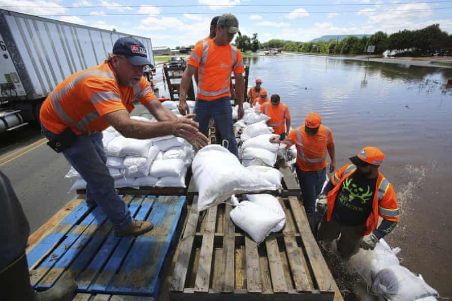 Workers lay down sandbags to keep water from flooding the entrance to a bridge across to Arkansas river in Russellville.