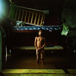 A girl stands in her flooded house