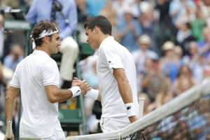 Roger Federer and Milos Raonic shake hands at the net.