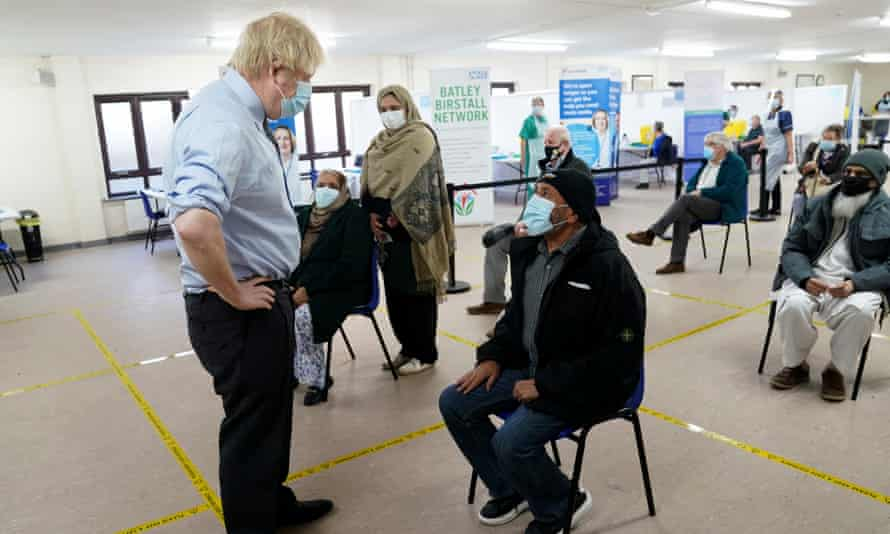 Boris Johnson talks to waiting patients at a Covid vaccination centre in Batley, West Yorkshire.