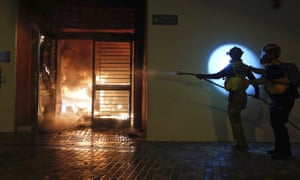 First aid volunteers work to extinguish a fire set by local residents at a building of the Fai Ming Estate, in the Fanling district of Hong Kong, after the Hong Kong government announced it would requisition the unoccupied housing project to house quarantined patients of the new viral coronavirus illness.