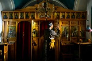 Ο πατέρας Ιουσίφ φωτίζει κεριά μέσα στην εκκλησία που έκτισε.