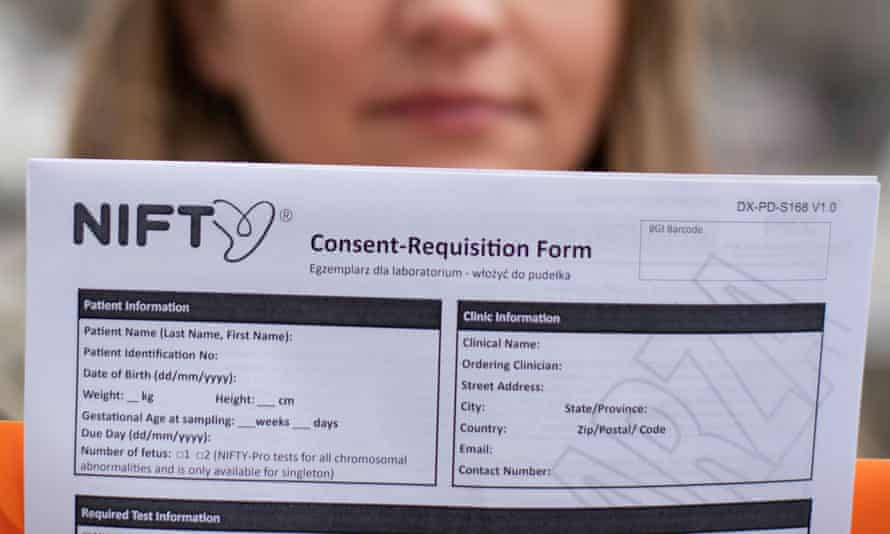 A woman who is pregnant and had taken Chinese gene firm BGI Group's Nifty prenatal test, holds a blank copy of the test's consent form in Warsaw, Poland, earlier this year.