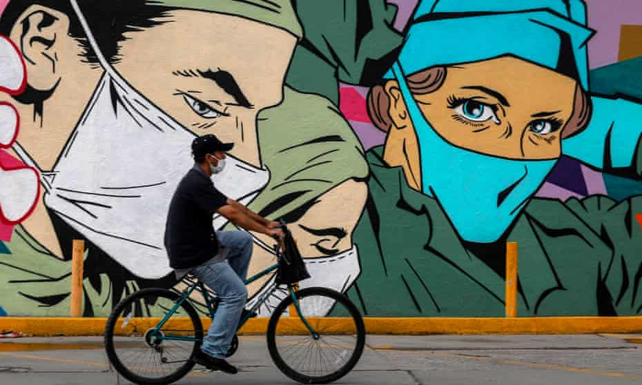 A man rides a bike past a coronavirus-related mural by urban artists Mick Martinez and 'Were Torres' in Ciudad Juárez, Chihuahua state, Mexico, at the weekend.