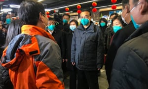 Li Keqiang , China's premier of the state council (centre), speaks to local residents as he visits a supermarket  in Wuhan