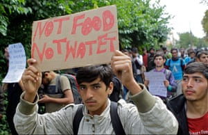 A man holds up a sign as he walks towards the Hungarian border in Serbia.