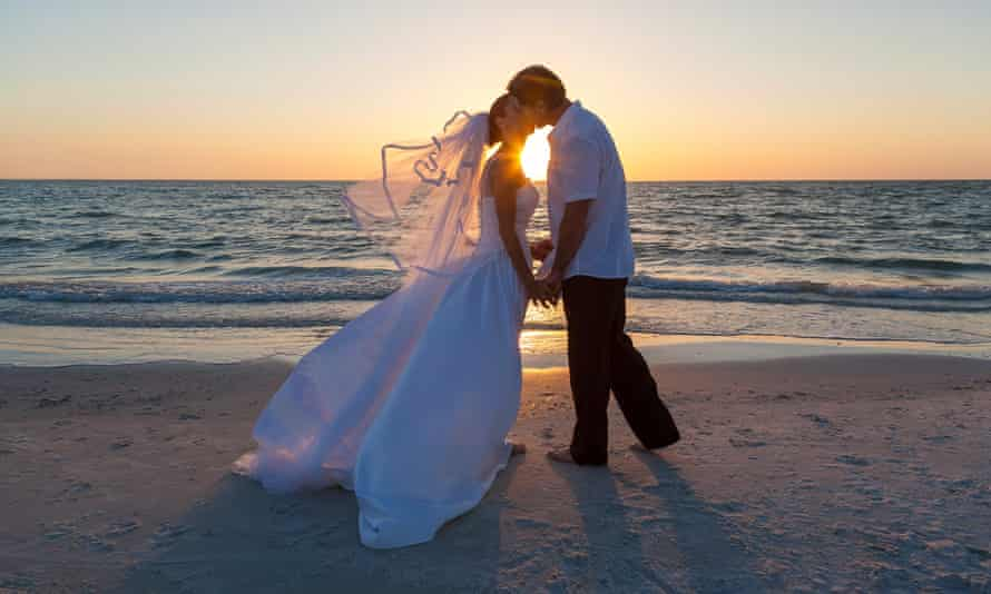 Bride and Groom Married Couple Sunset Beach WeddingPosed by models A married couple, bride and groom, kissing at sunset or sunrise on a beautiful tropical beach