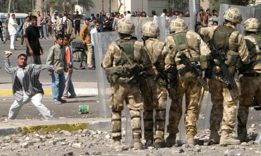 Hearts and minds … a youth hurls a rock a British soldiers during a violent protest by job seekers in Basra, March 2004.