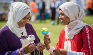 The Muslim Festival Of Eid al-Fitr Is Celebrated Around The UKLONDON, ENGLAND - JULY 06: Women eat ice cream as people celebrate the festival of Eid at Southwark Eid Festival in Burgess Park on July 6, 2016 in London, England. Thousands gathered at Southwark Eid Festival in Burgess Park to celebrate the Muslim holiday of Eid which marks the end of 30 days of dawn-to-sunset fasting during the holy month of Ramadan. (Photo by Rob Stothard/Getty Images)