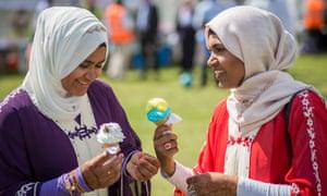 Women eat ice cream at Southwark Eid festival in Burgess Park, south London.