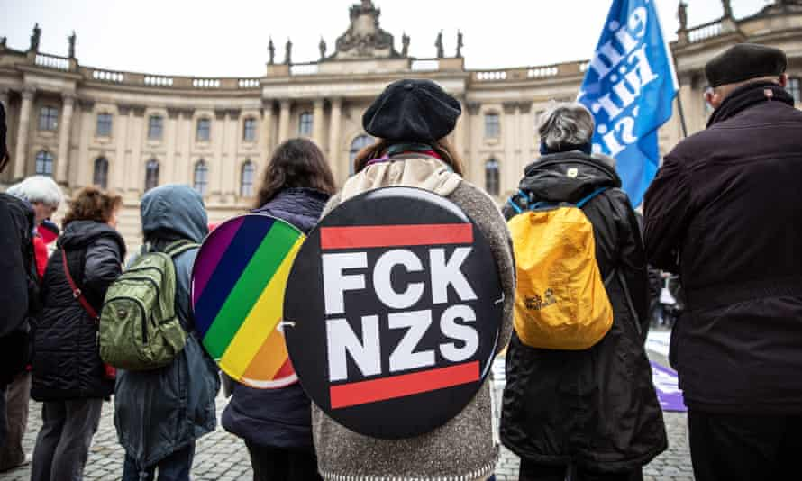 A leftwing counter-protester with a banner reading 'FCK NZS' takes part in a demonstration against the march of the far-right group 'Reichsbuerger' in Berlin, Germany, on 9 November.