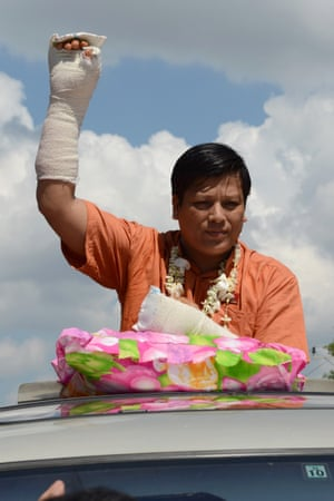 Naing Ngan Linn waves with his bandaged arm to supporters during a campaign in Tharketa township in Yangon.