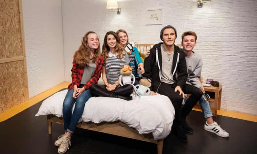 Fans pose for pictures with waxwork figures of vloggers Zoe Sugg and Alfie Deyes
