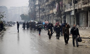Syrians leave a rebel-held area of Aleppo to go to the government-held side.