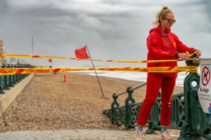 Abbie, a lifeguard, puts up tape to prevent people accessing the beach at Hove