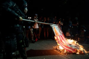 A protester burns a flag during a demonstration against police violence and racial inequality in Portland.