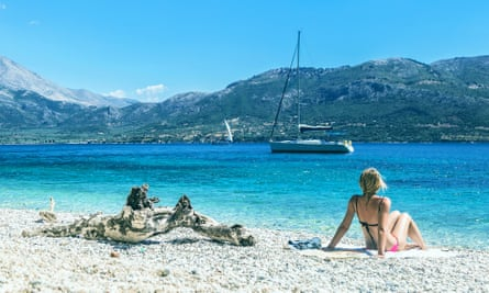 Sunbather on beach looking at a sailboat