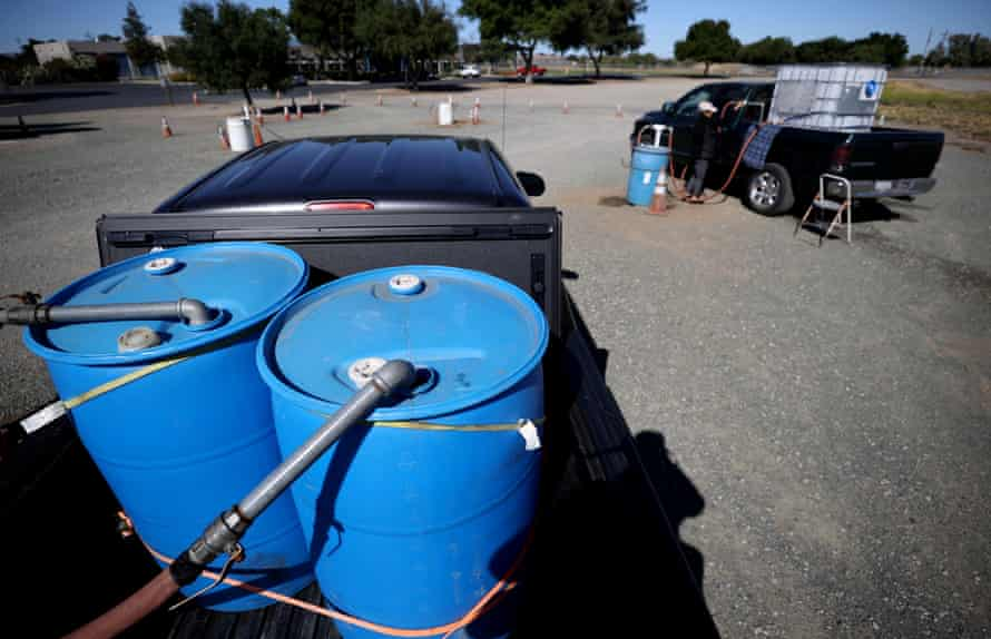 Un résident remplit un réservoir d'eau avec de l'eau recyclée provenant d'une station de remplissage à Oakley.