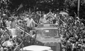 Members of the five-man junta of the Sandinista provisional government wave from the top of a fire truck as they enter the main square in downtown Managua, 1979.
