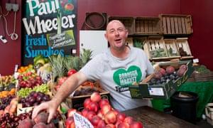Paul Wheeler at his veg stall, placing a peach from a box
