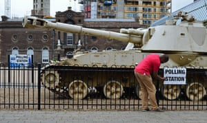 A polling clerk secures a polling station sign to a fence enclosing a 2S3 M-1973 Akatsiya 152-mm self-propelled gun howitzer, standing outside the Greenwich Heritage Centre, set up as a polling station, in London