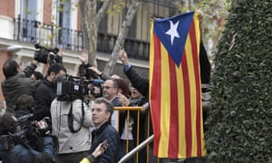 A protester holds a Catalan flag as members of the deposed Catalan regional government arrive at the national court in Madrid.