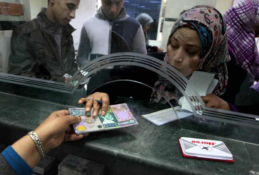 A Libyan bank cashier gives a client outdated bank notes, which had been removed from circulation and reissued due to cash shortage in Tripoli in 2011.
