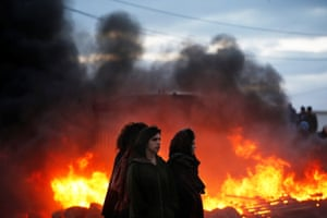 Amona, West Bank Protesters stand next to fires